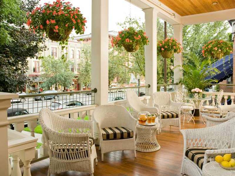 View of the porch lined with white wicker furniture at Saratoga Arms