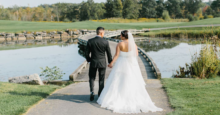 a bride and groom about to walk over a bridge on a golf course
