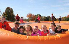 kids on a pumpkin jumping pillow at ellms farm