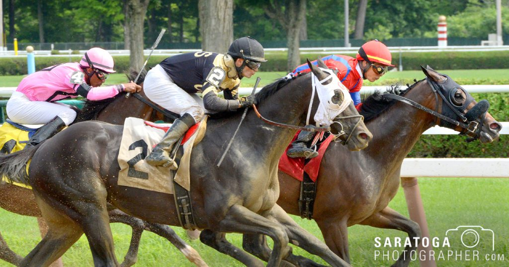 three horses and riders racing