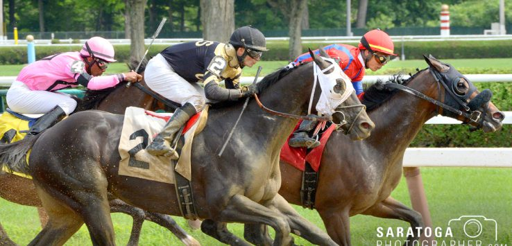 three horses and riders racing