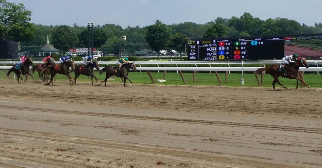 horses racing down a dirt track
