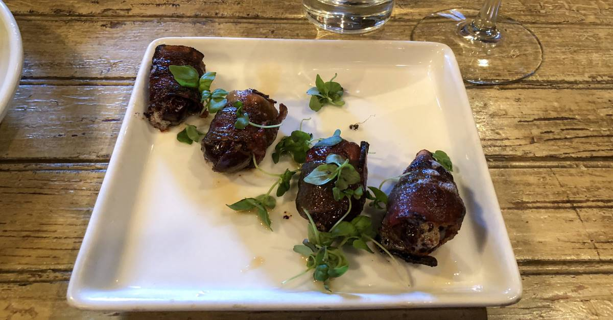 Four bacon wrapped dates on a small square plate