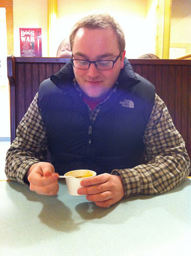 man with glasses eating small cup of chowder