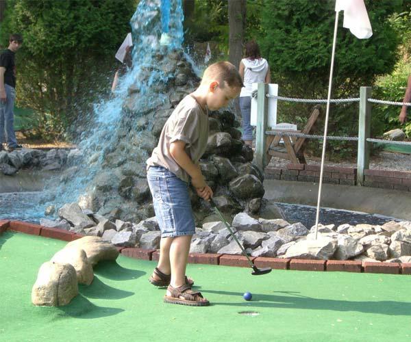 kid playing mini golf