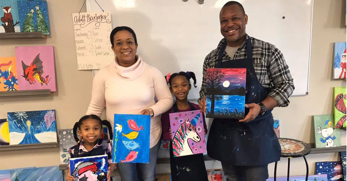 family of four holding up paintings