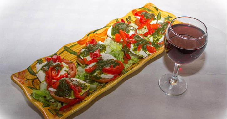appetizer of tomato, lettuce, basil, and mozzarella cheese on a rectangular wooden plate with a glass of red wine