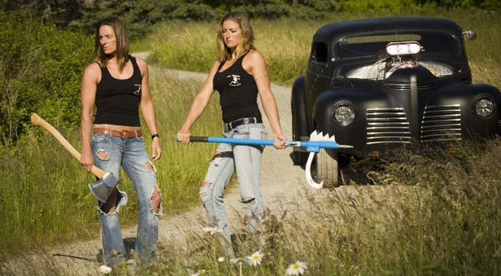 two tough and fit looking women with jeans and black tank tops holding axes standing on a path in the woods with a black old fashioned car behind them
