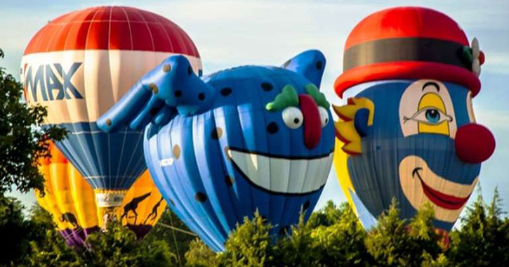 three hot air balloons, two with goofy faces