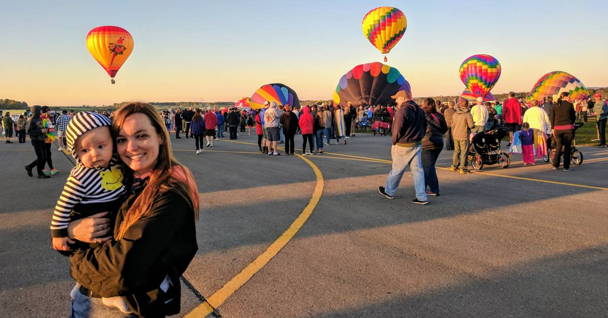 a woman with her baby posing at the balloon festival, balloons taking off in the background