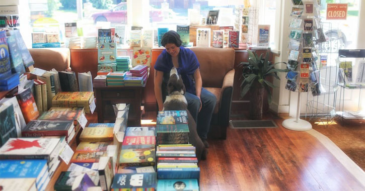 a woman sitting with a dog in a bookstore in front of a window