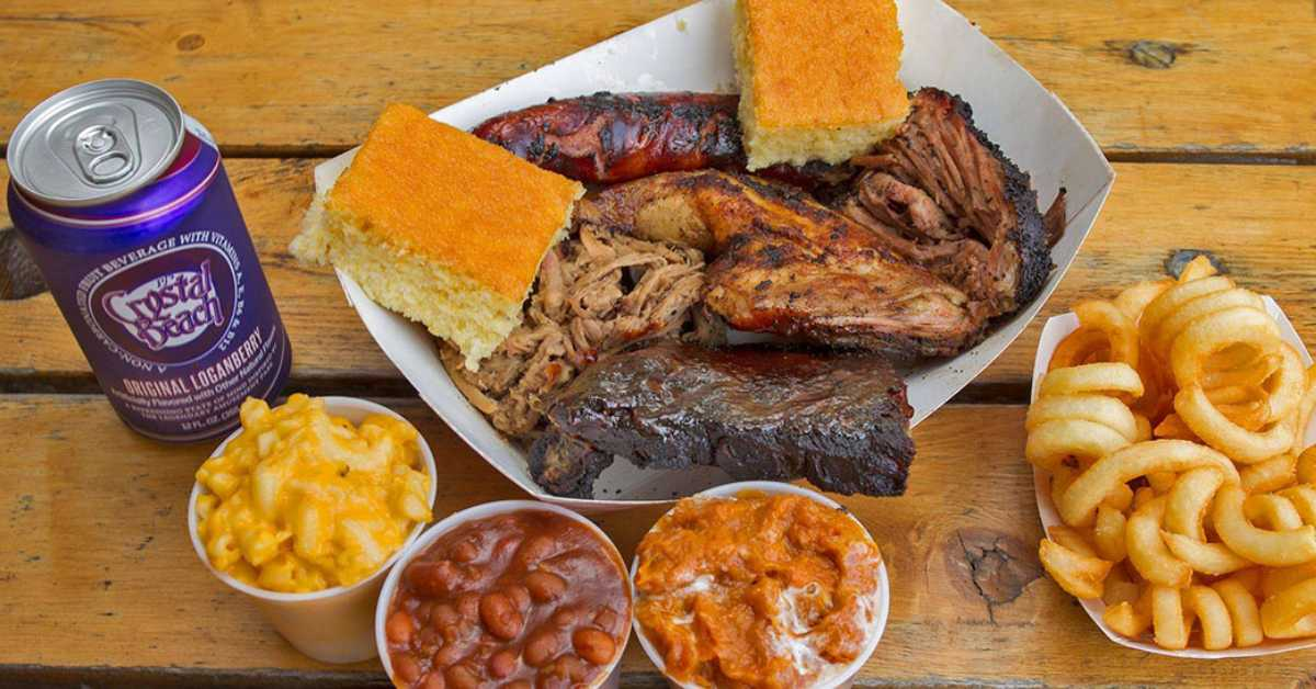 bbq meat and corn bread, onion rings, sides, and a drink