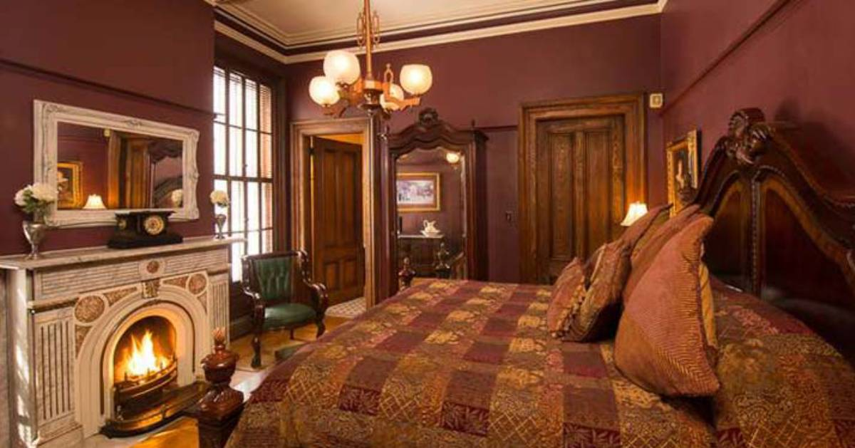 ornate guest room with a fireplace at the foot of the bed