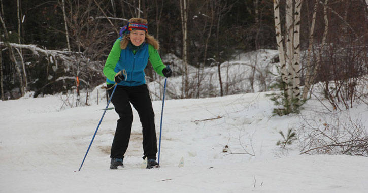 a woman skiing down a small hill