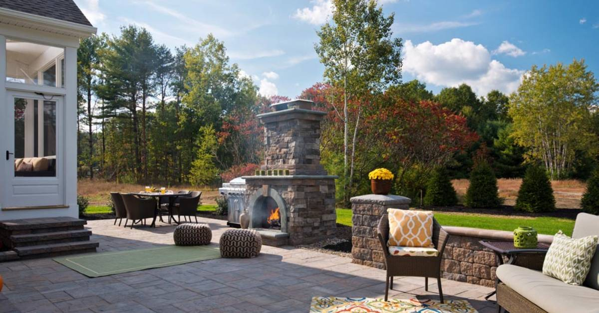 paver patio with furniture and a fireplace