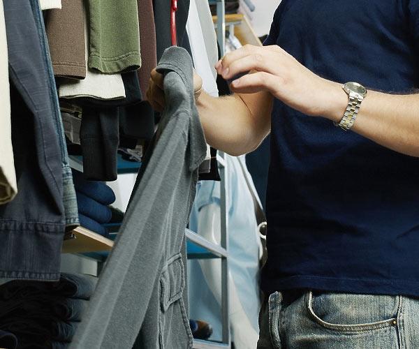 man picking out a shirt