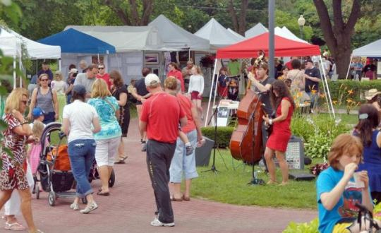 people walking through park art fair