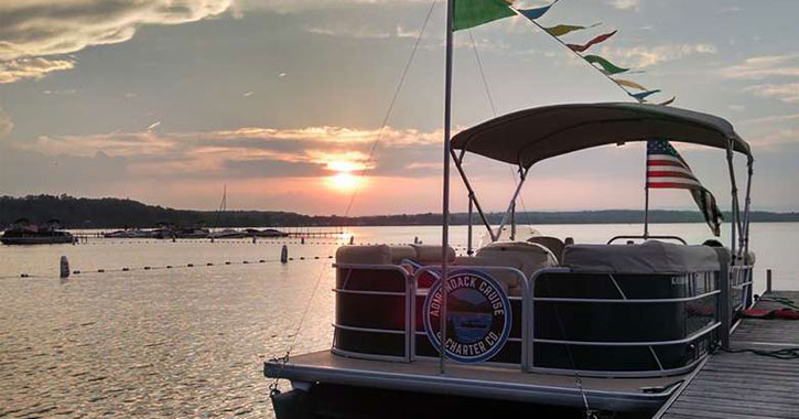 an Adirondack Charter Cruise boat at the dock on Saratoga Lake at sunset