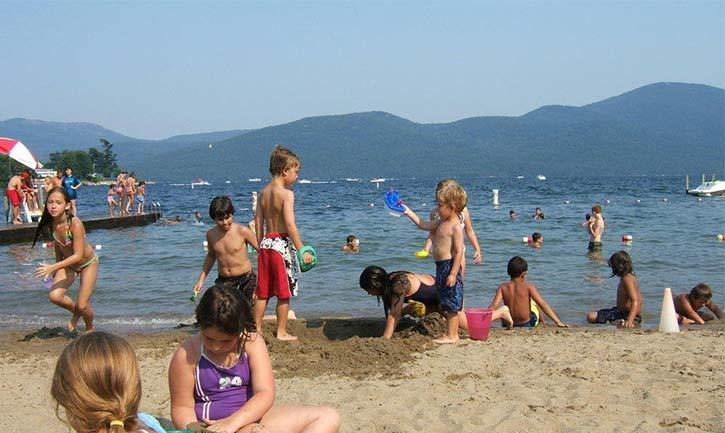 kids playing on a Bolton Landing beach