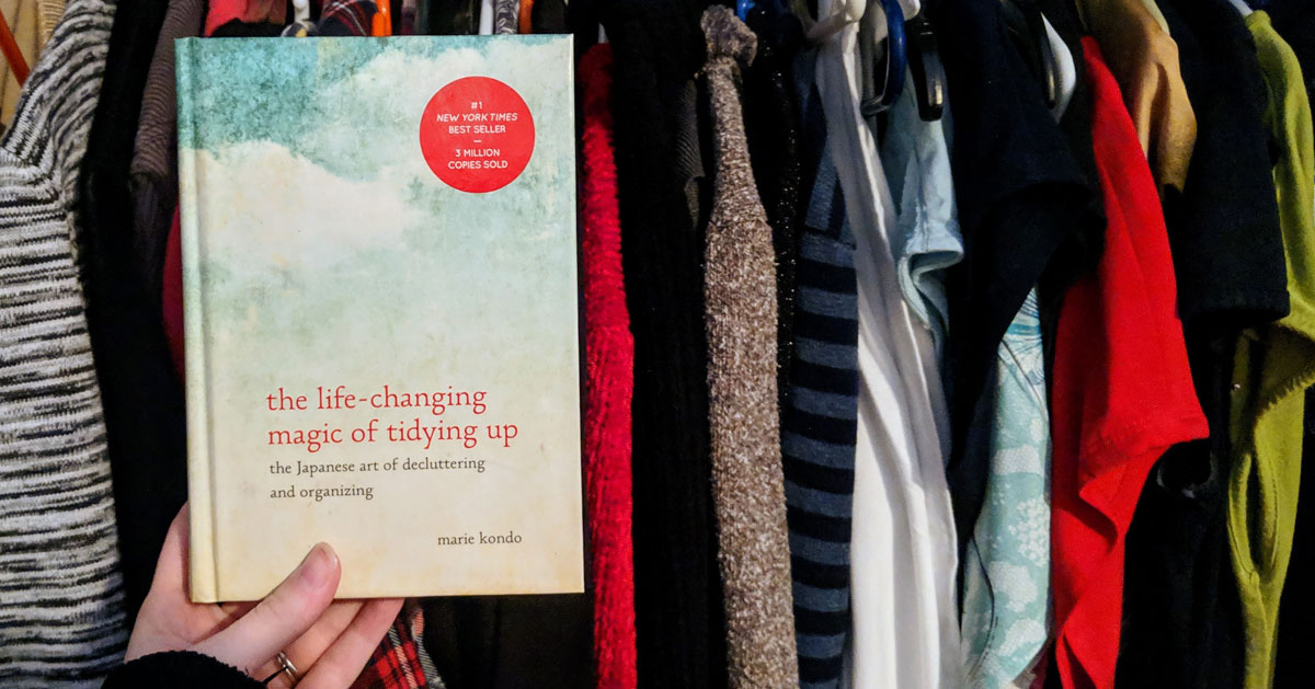 the Marie Kondo book held out in front of a closet of clothes