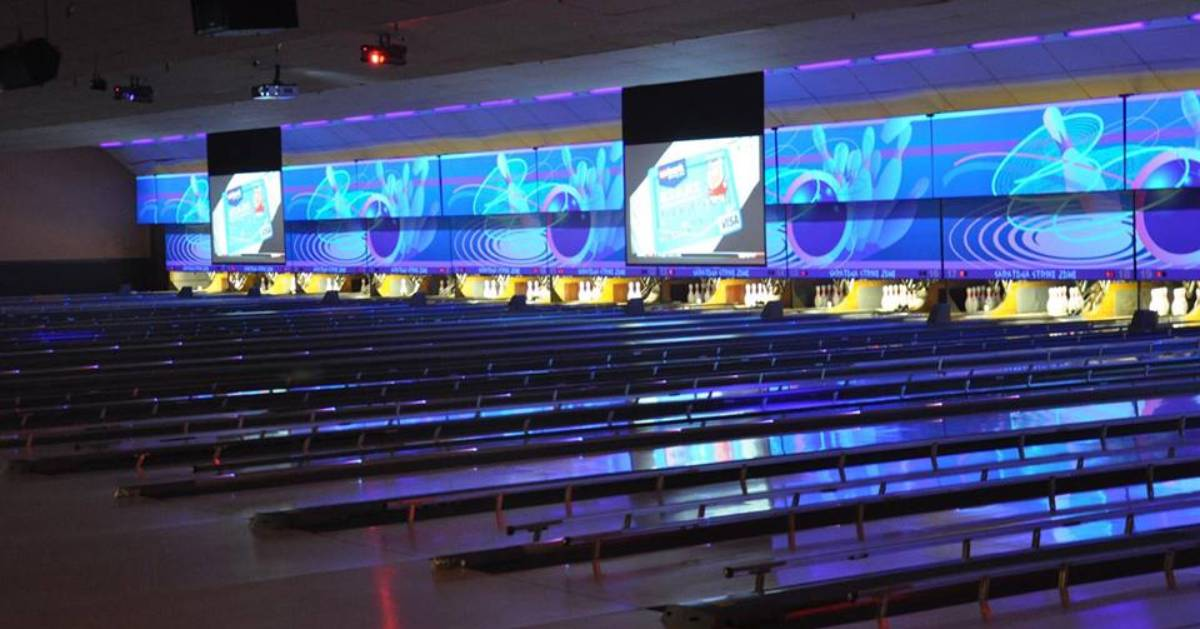 bowling alley with colorful lights above lanes