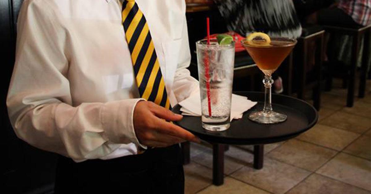 waiter bringing over cocktails