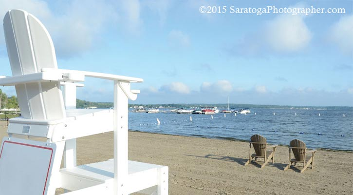 view of the water at Browns Beach with a white lifeguard chair to the left and two brown Adirondack chairs in front