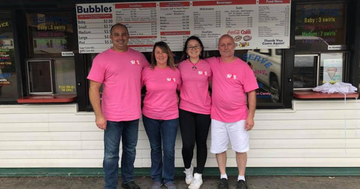 four people in pink shirts in front of ice cream window