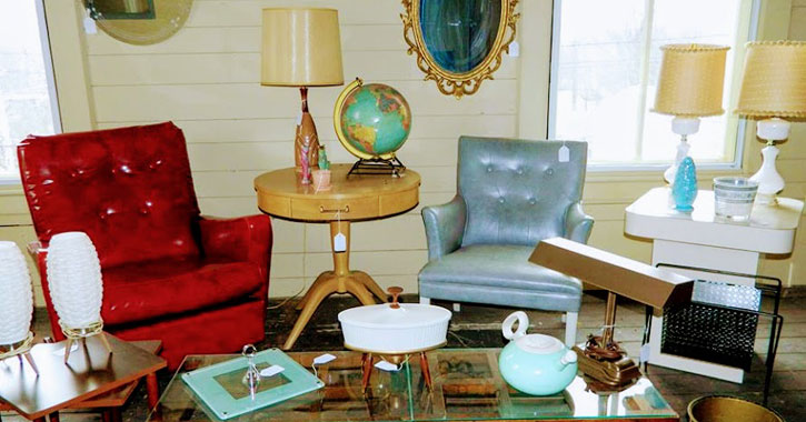 items in an antique store, including chairs, lamps, and items on a coffee table