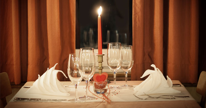 a table setting for candlelit dinner for two with a heart decoration under the candle