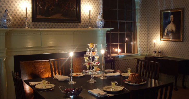 an old fashioned dining room, dark with candles lit
