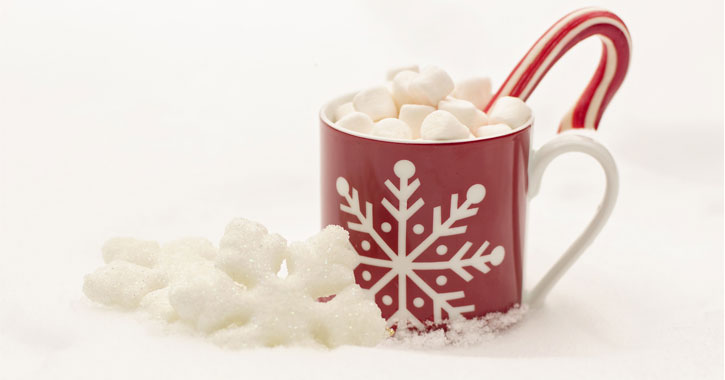 red coffe cup with white snowflake on it holding cocoa with marshmallows and a candy cane