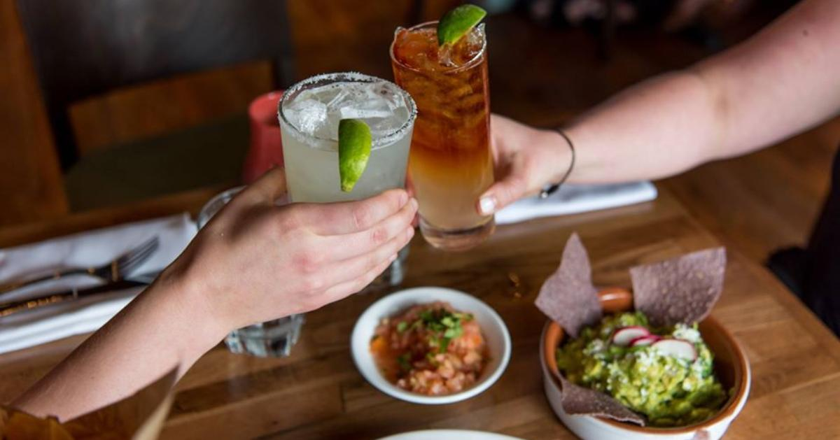 two people raising drinks over bowl of guacamole and chips