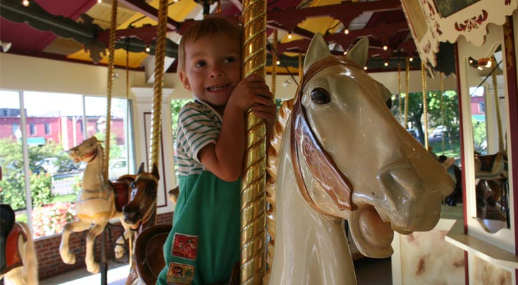 little boy riding the carousel