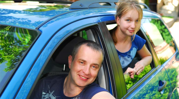 dad and daughter hanging out the car windows, smiling