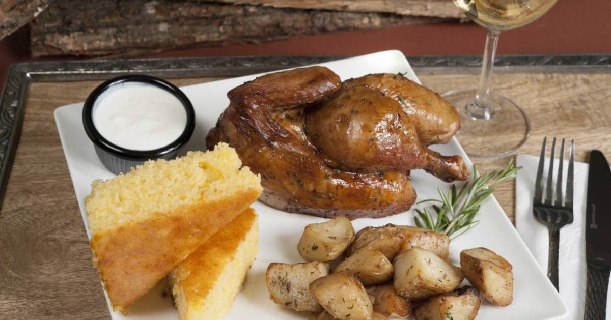 white dinner plate with rotisserie chicken, potatoes, and corn bread
