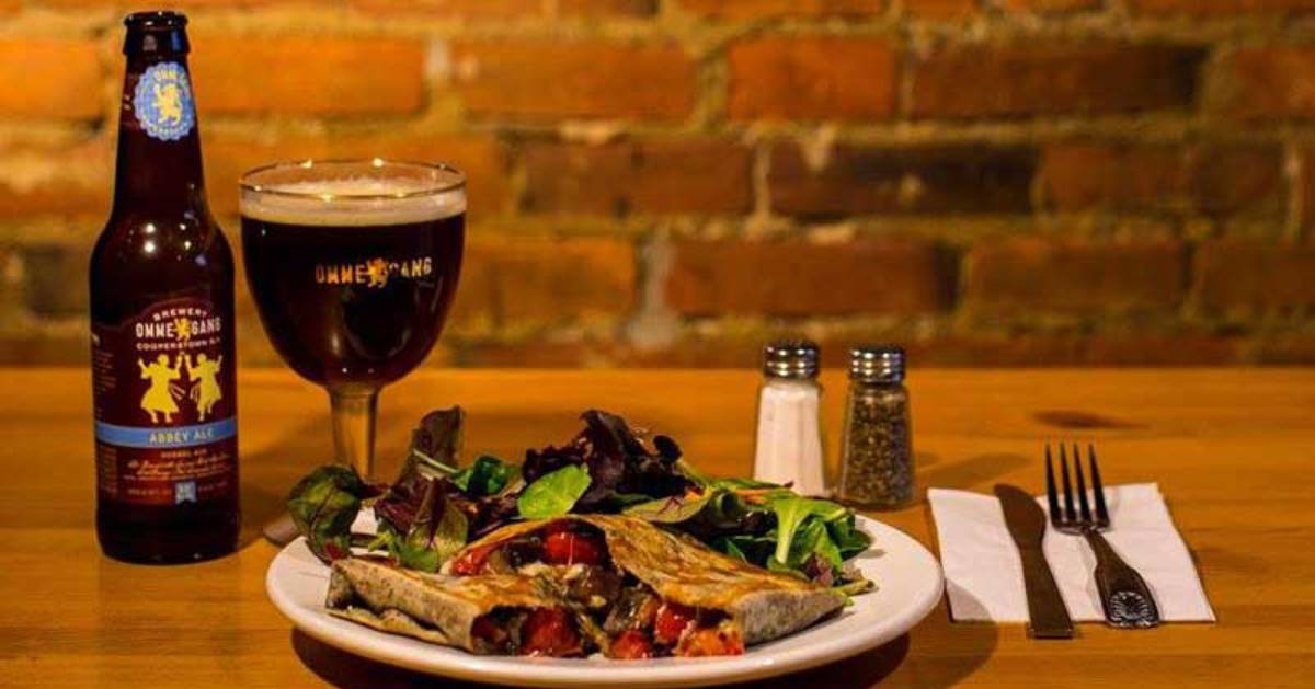 beer bottle, glass of beer, and crepe dinner on plate
