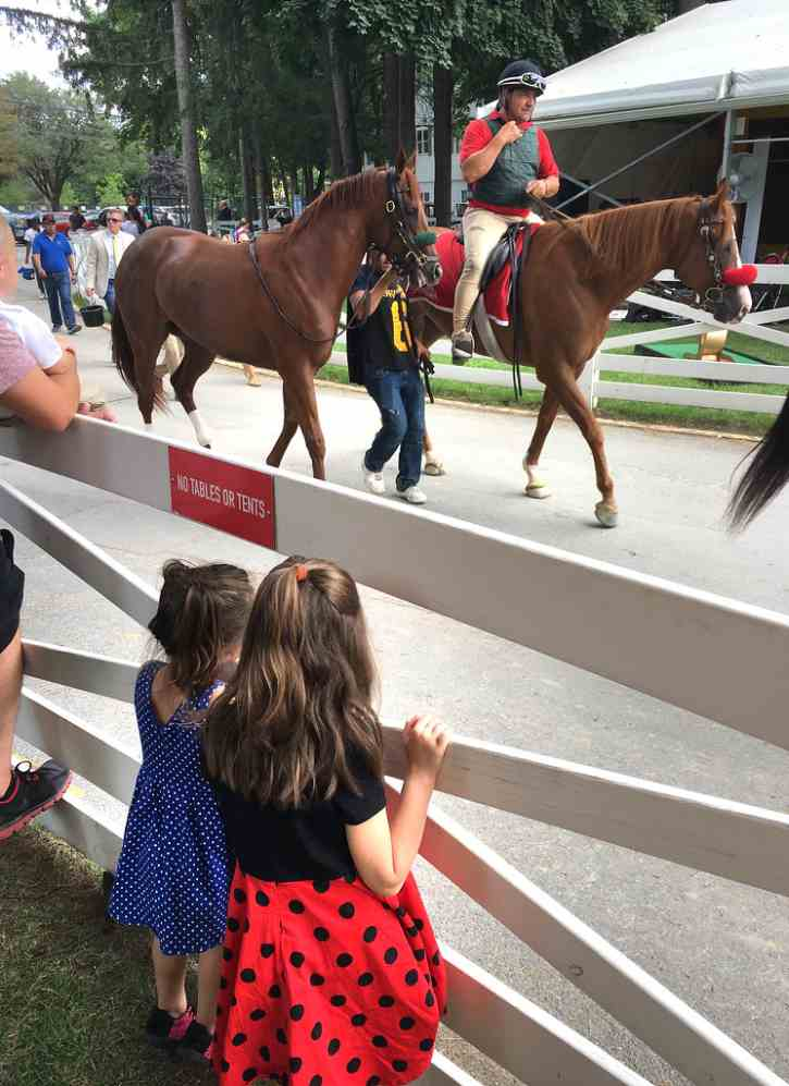 children watching horses walk by at the track