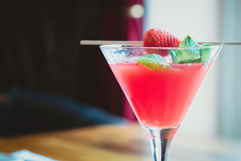 a red cocktail in a martini glass with a strawberry