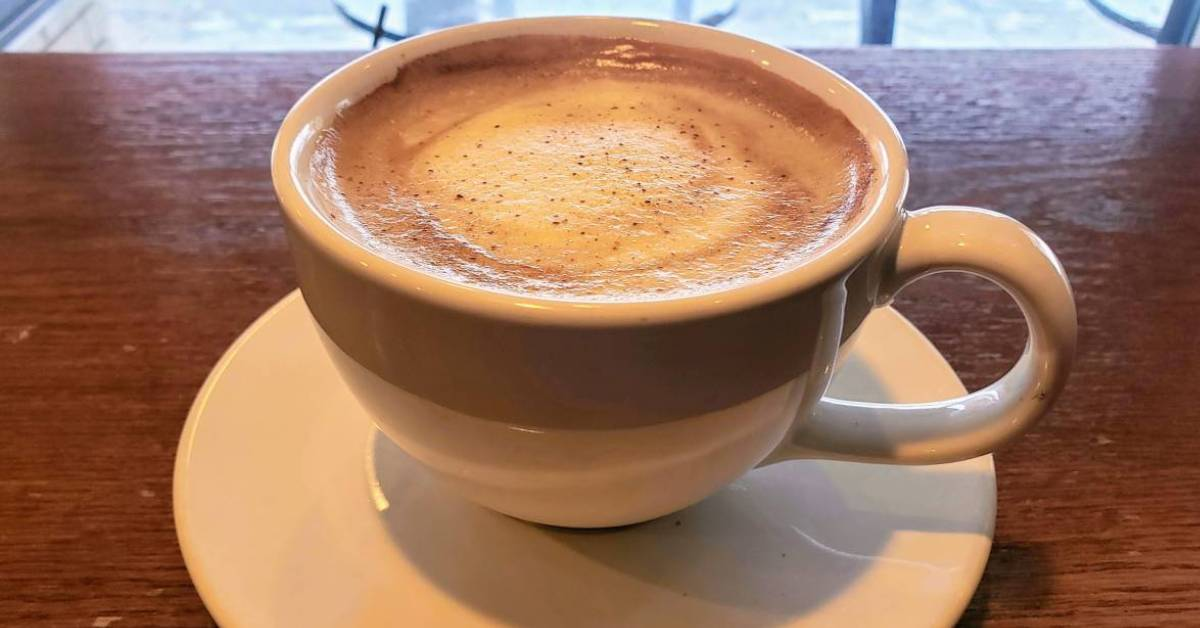 a cup of coffee with froth on top