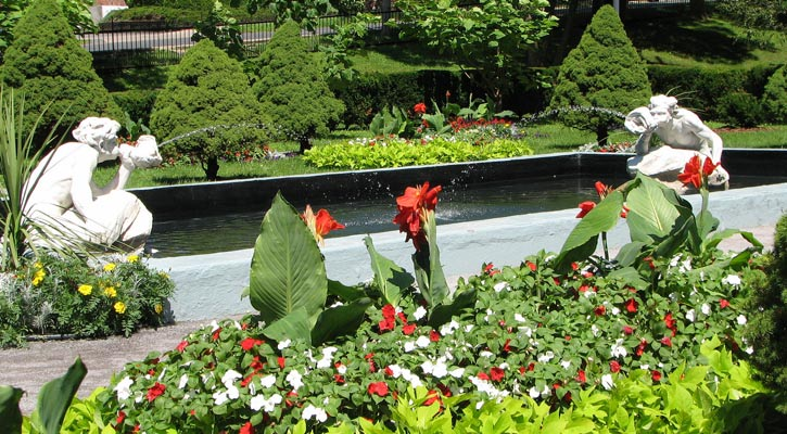 in the park, two angel statues spraying water, beautiful plants and red and white flowers