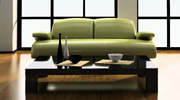 green couch behind brown coffee table with hardwood floors and floor to ceiling windows behind