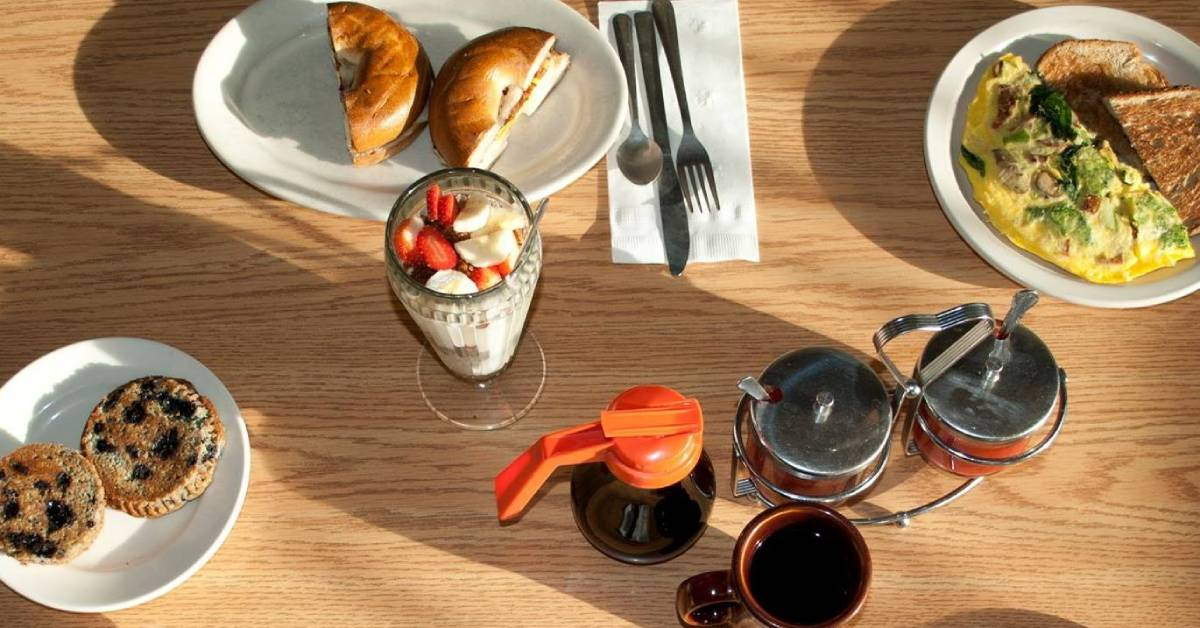 fruit, muffins, a bagel sandwich and other breakfast food on a table