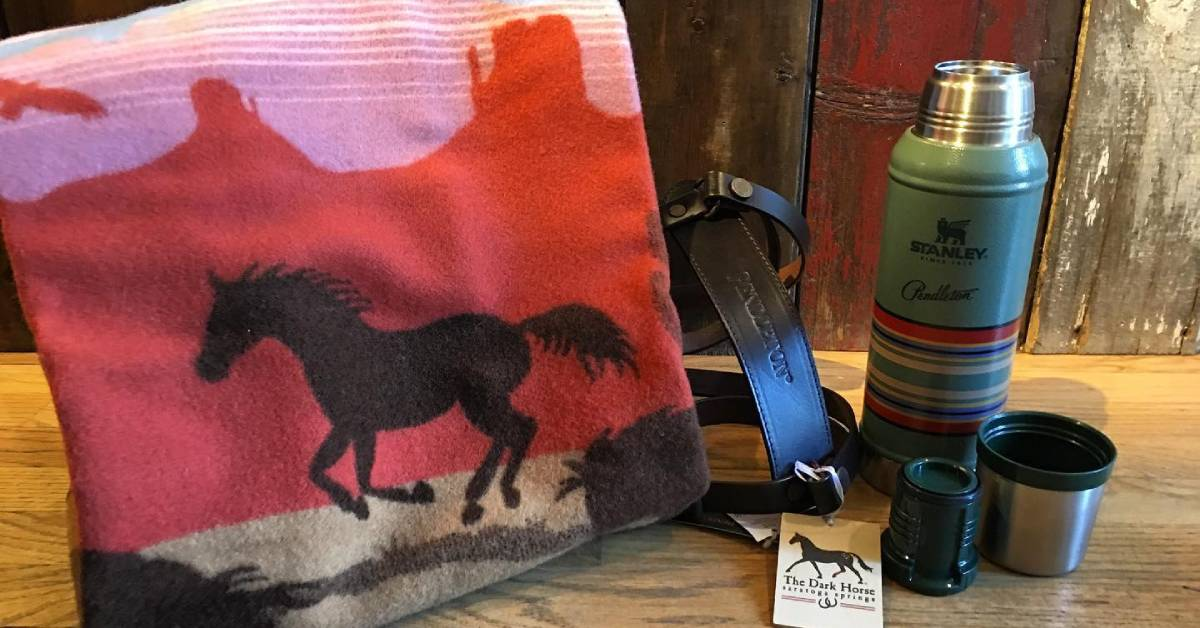 a folded blanket with a black horse image next to a thermos