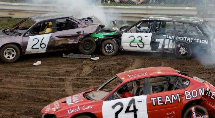 three cars, one crashing into another one in a demolition derby