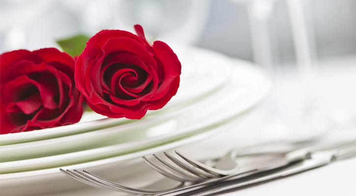 close up of roses next to a white dinner plate