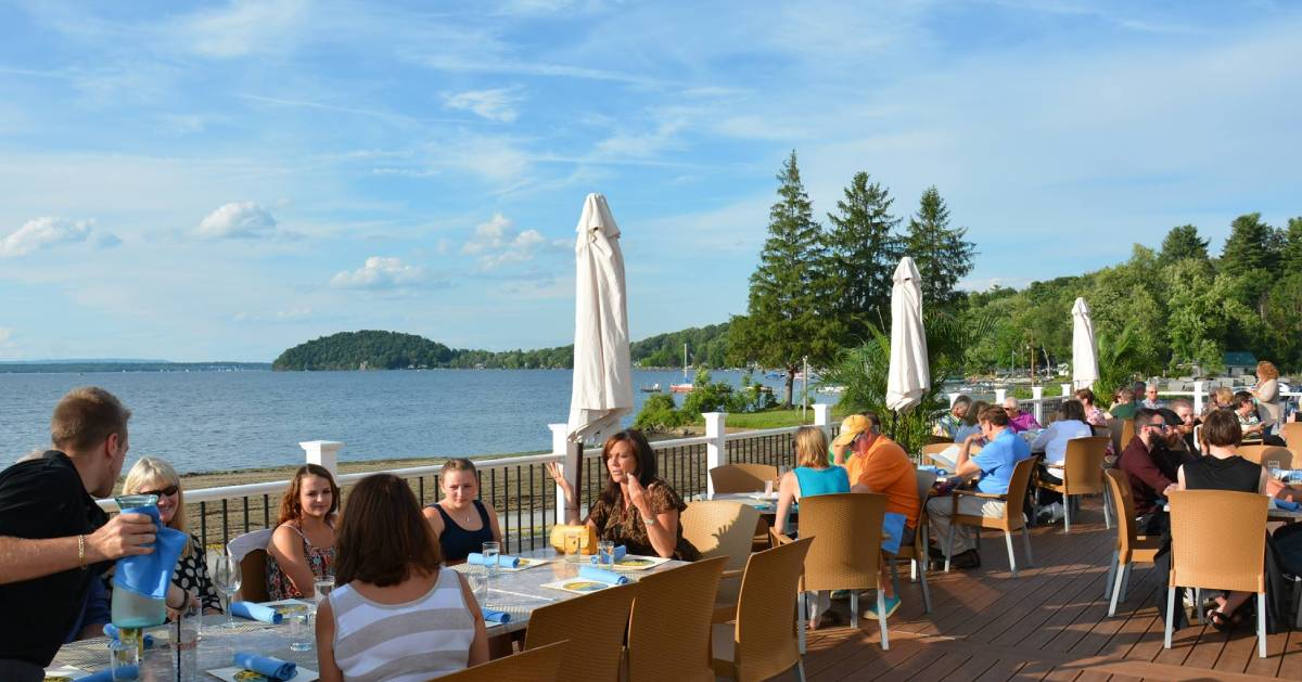 people dining on a patio by the lake