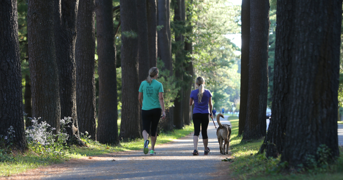 two women and a dog walking
