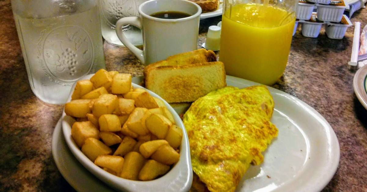 eggs, toast, potatoes, water, and coffee on a table