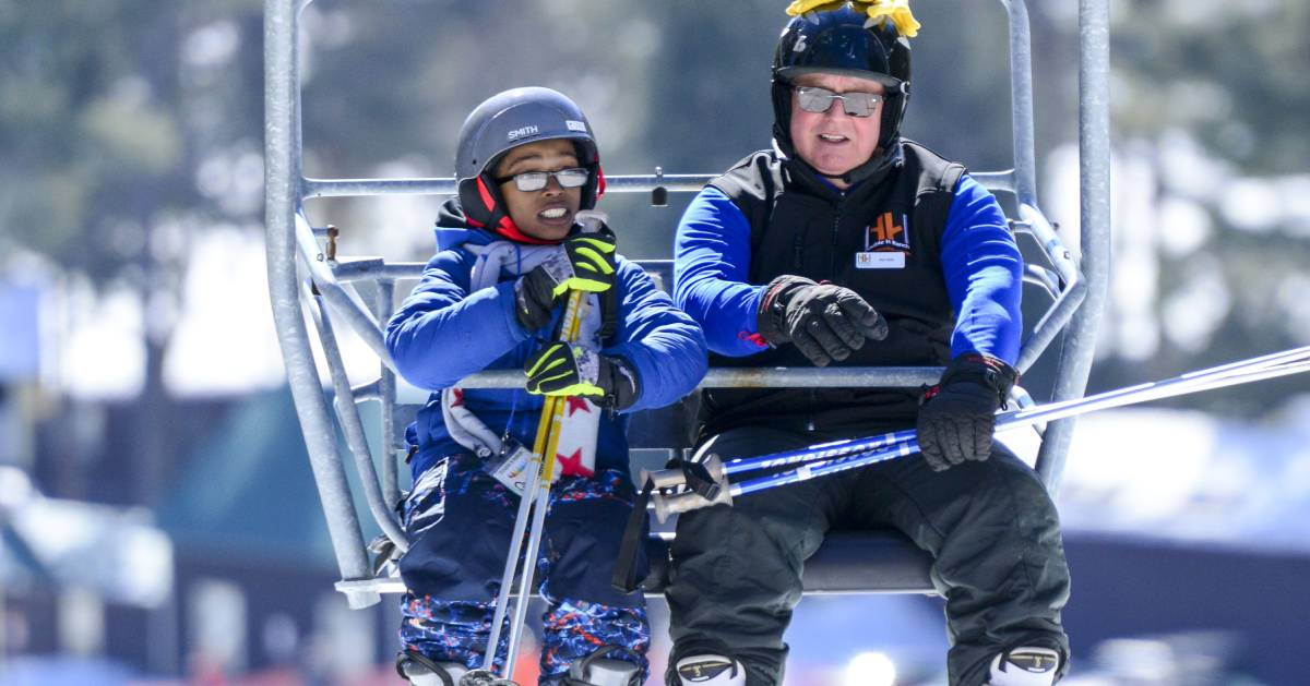 a child and a volunteer riding a ski lift at double h ranch